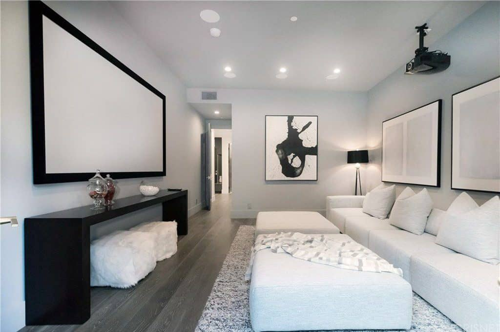 This Home Features A Media Room With White Sofa Set And Stylish Wall Decors Lighted By