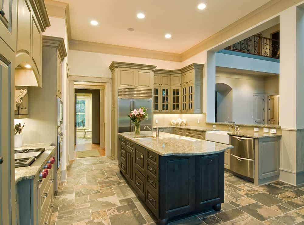 Large Mediterranean kitchen featuring a tiles flooring, white walls and a large center island topped by a marble countertop.