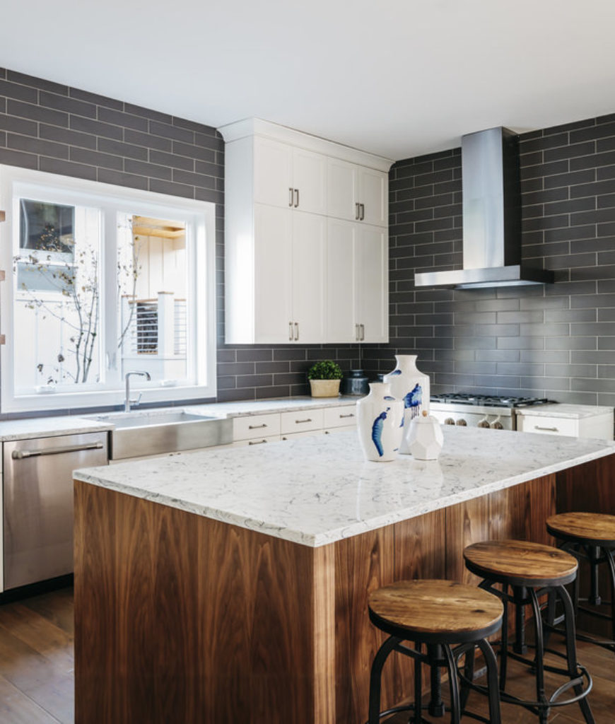 Kithcen with dark gray walls, white countertops and island that seats 3 people.
