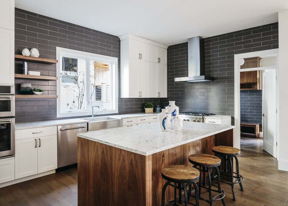 Kithcen With Dark Gray Walls, White Countertops And Island That Seats 3  People. |