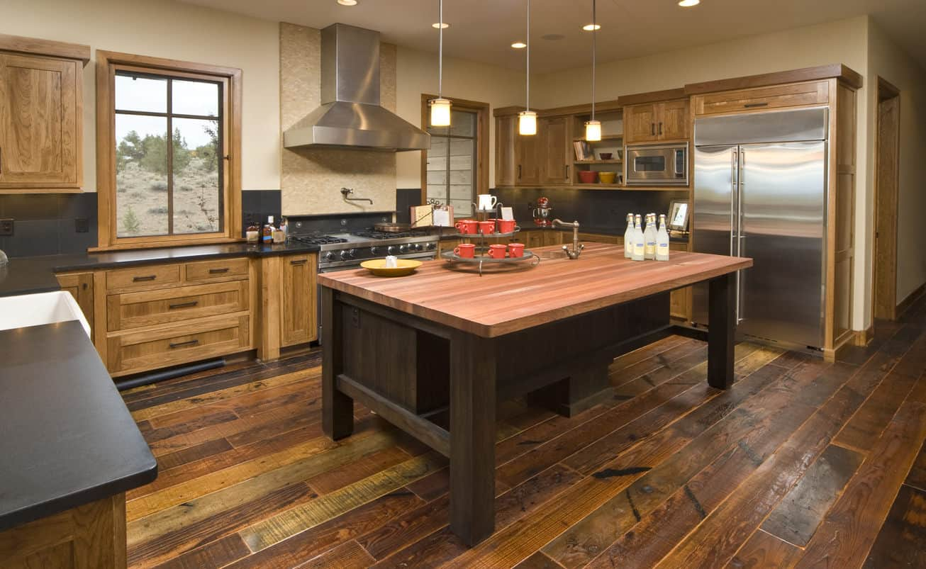 Rustic kitchen with wooden cabinetry, rustic wooden flooring, and a wooden kitchen island.