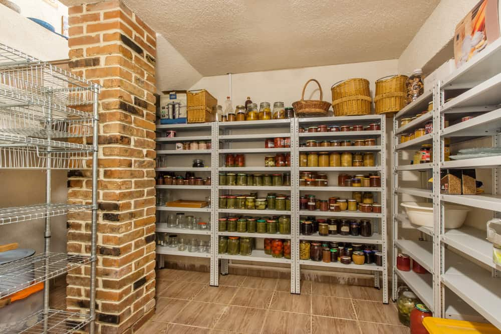 Large kitchen pantry featuring tiles flooring and a brick pillar.