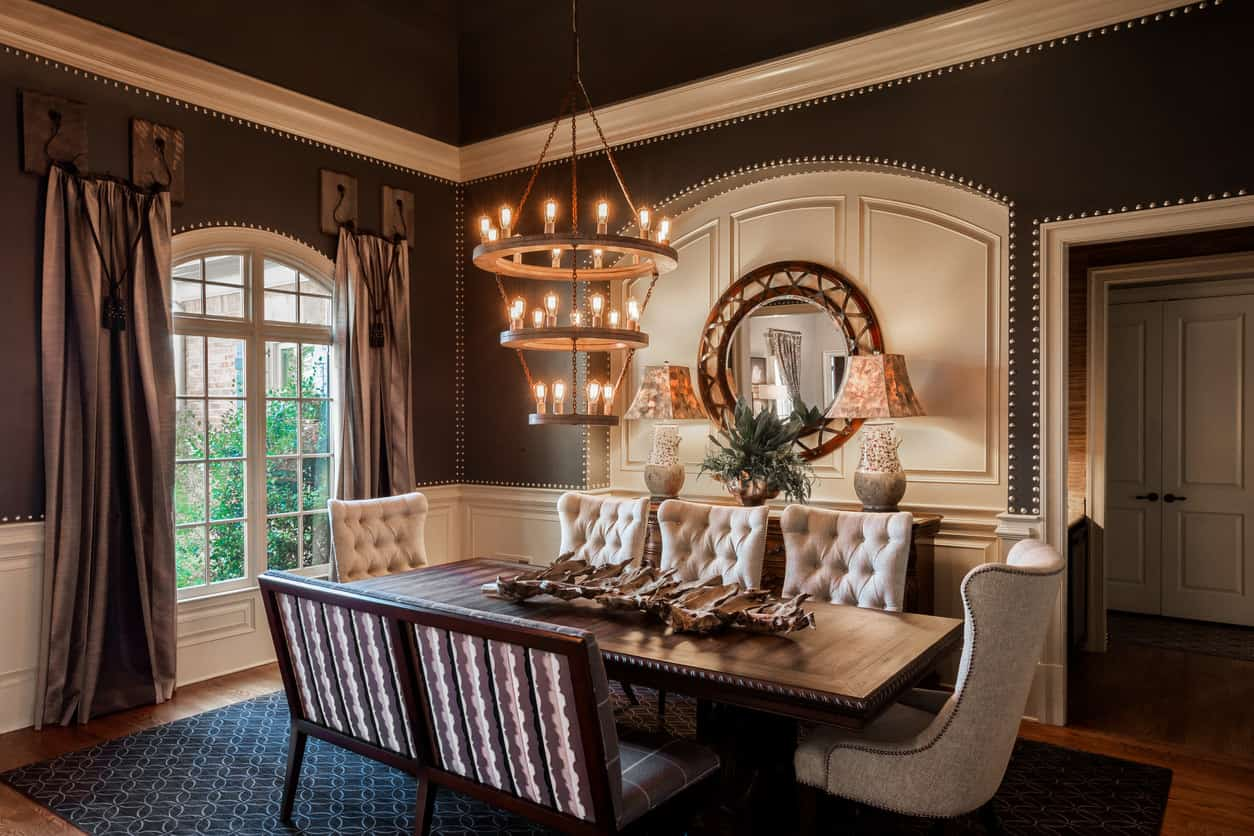 A very classic dining room with a luxurious feel showcasing mismatched chairs and an intricate dining table lit by a three-tier chandelier. It has an arched window and wainscoted walls mounted with a gorgeous round mirror that hung above a wooden buffet table.