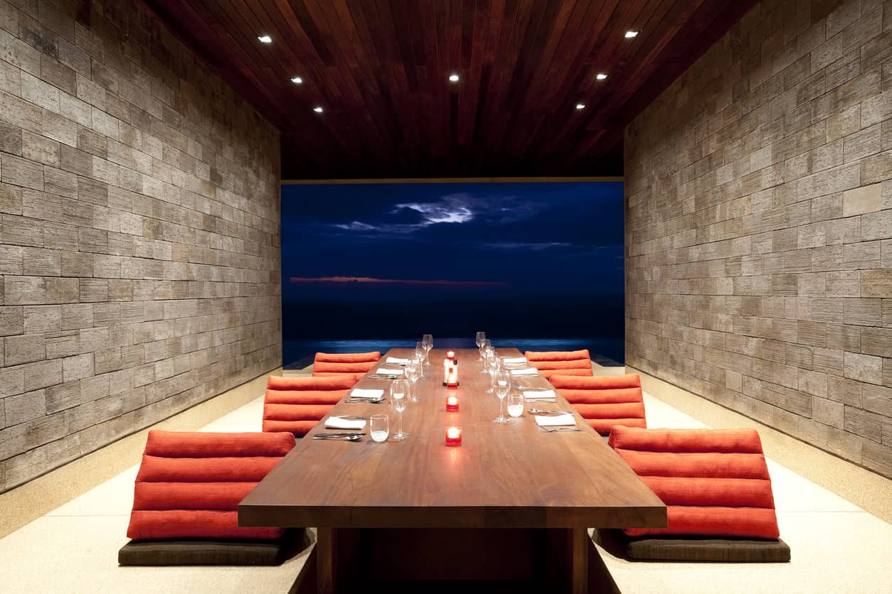 This one is a simple yet sleek dining room with brick walls and wood plank ceiling fitted with recessed lights. It has unique chairs and a long dining table facing a magnificent view.
