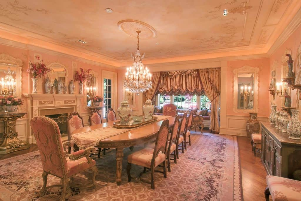 Charming dining room filled with ornate tables and elegant seats along with a glamorous crystal chandelier that hung from the tray ceiling. It is decorated with ceramic vases and lovely mirrors mounted above the white wainscoting.