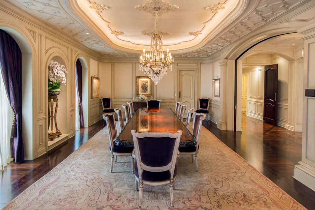 Large dining room with arches and dark hardwood flooring topped by a classic area rug. It is filled with a long dining table and a pair of crystal chandeliers that hung from the stunning tray ceiling with ornate detailing.