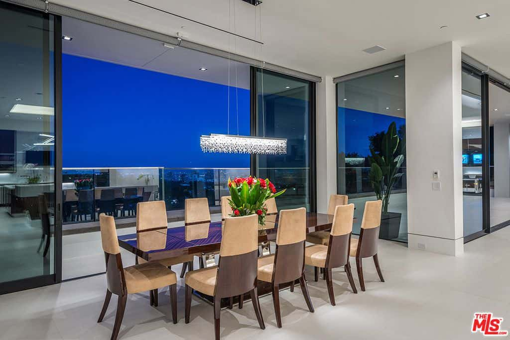 A linear chandelier illuminates the wooden dining set in this modern dining room with tile flooring and glass sliders that open to the balcony with an expansive view.