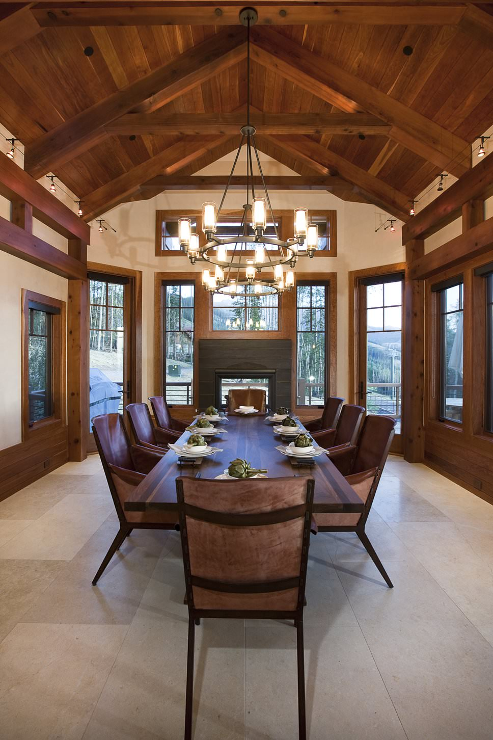 A dark wood dining set complements the moldings and a cathedral ceiling that's clad in natural wood planks. It is illuminated by round chandeliers along with natural light flowing in from the glazed windows.