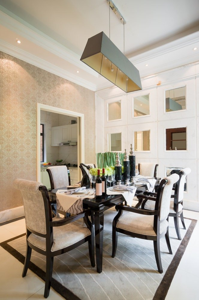 This dining room is designed with a stylish mirrored wall and fleur patterned wallpaper that gives a classic look. It features a glossy black dining table and beige cushioned chairs that sit on a gray area rug.