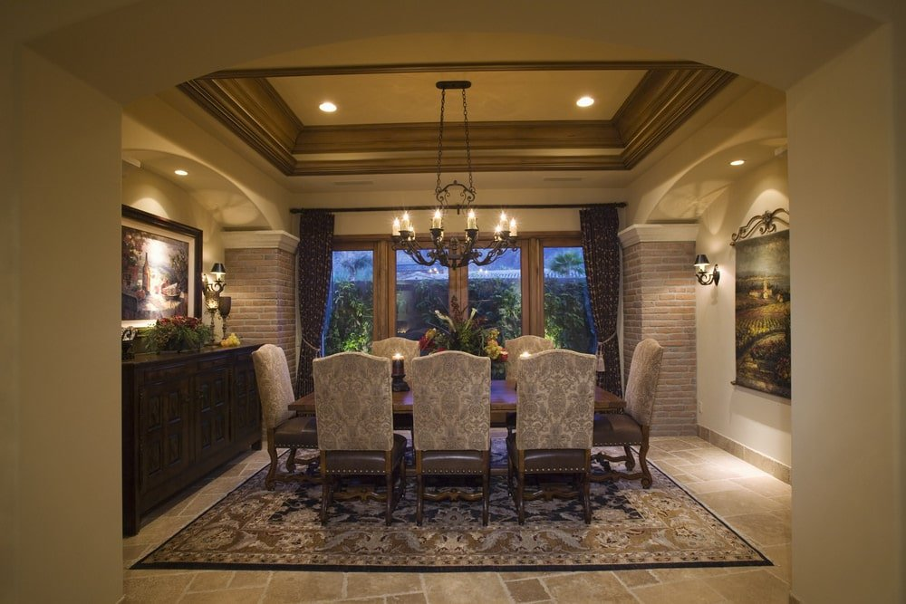 Ambient light from the wall sconces and wrought iron chandelier creates a warm and romantic vibe in this dining room with limestone flooring and full height windows dressed in patterned drapes. It has a classy dining set over a printed rug situated in between arched insets.