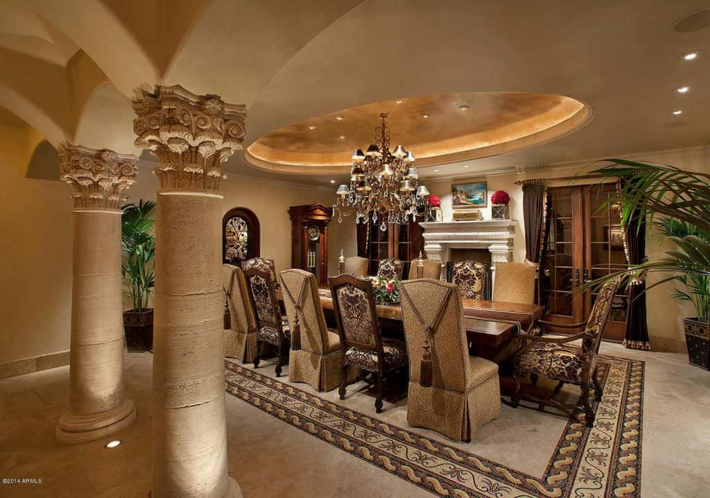 Large potted plants softened the architectural design of this dining room with a tray ceiling and Greek columns that blend in with the beige floor accented with a bordered centerpiece. It is furnished with a wooden dining table and alternating skirted and floral chairs.