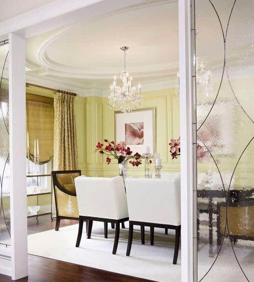 Luxury dining room enclosed in frosted glass panels and wainscoted walls accented with floral artworks. It has crystal chandeliers and sleek dining set over a beige area rug matching with the cushioned chairs.