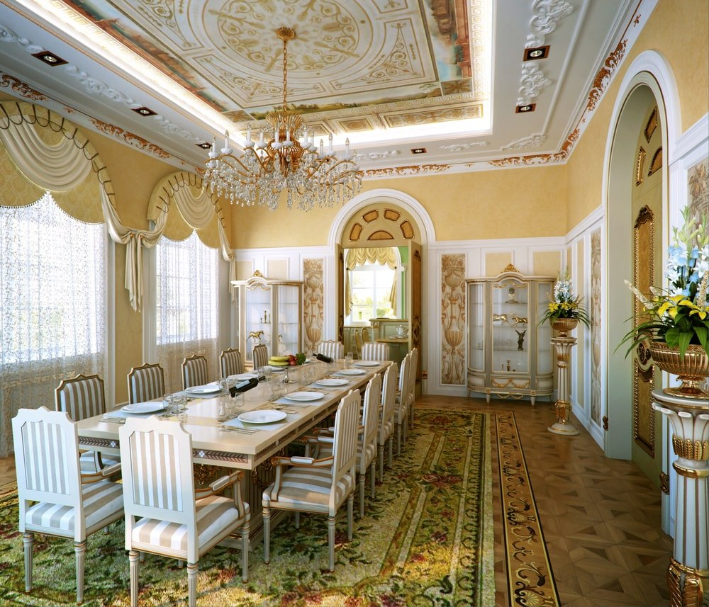 This dining room has a yellow color scheme with subtle green and gold accents. Flower pedestals and a fabulous crystal chandelier add elegance in the room.