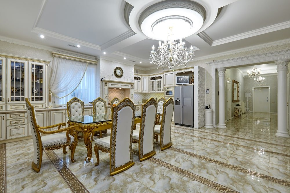 A spacious dining area with tile flooring and a tray ceiling mounted with recessed lights and a grand chandelier. It showcases a glass top dining table and elegant tufted chairs with high back features.