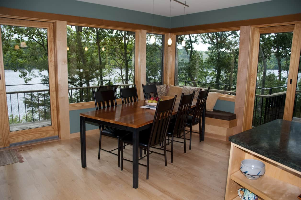 Casual cabin style dining room with view of forest.