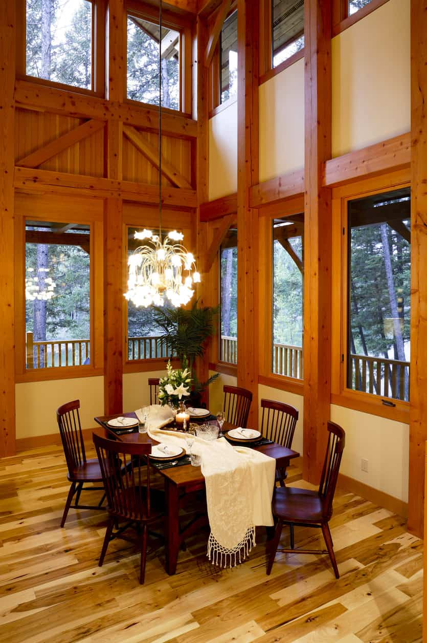 Large dining room space with surrounding windows and plenty of natural wood.