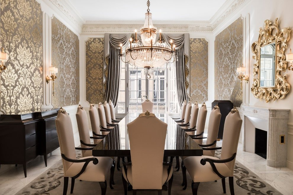 A dining room that's full of class starting from the ornate mirror and wainscoted walls that are clad in fleur patterned wallpaper up to the marble fireplace and dark wood furniture. It is illuminated by drum sconces and a beaded chandelier that hung from the ornate ceiling.
