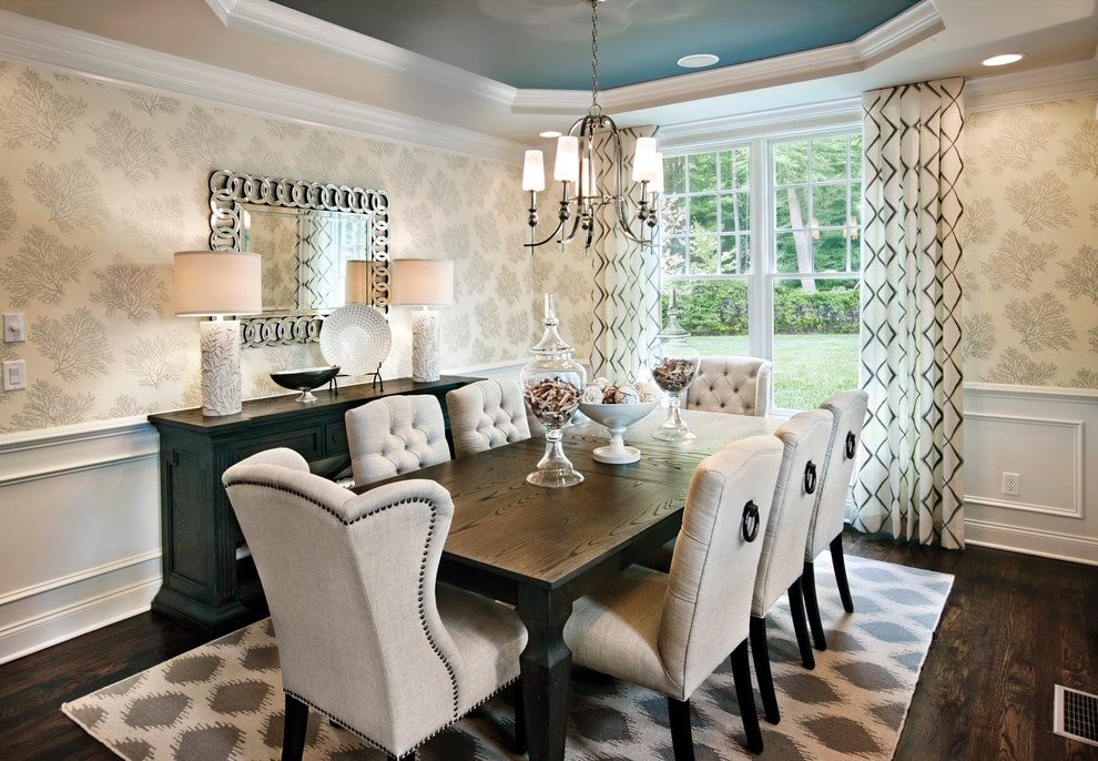 A stylish framed mirror adds a nice accent in this dining room with a blue tray ceiling and wainscoted walls clad in floral wallpaper. It has a black buffet table and beige tufted chairs surrounding the rectangular dining table that complements the dark hardwood flooring.