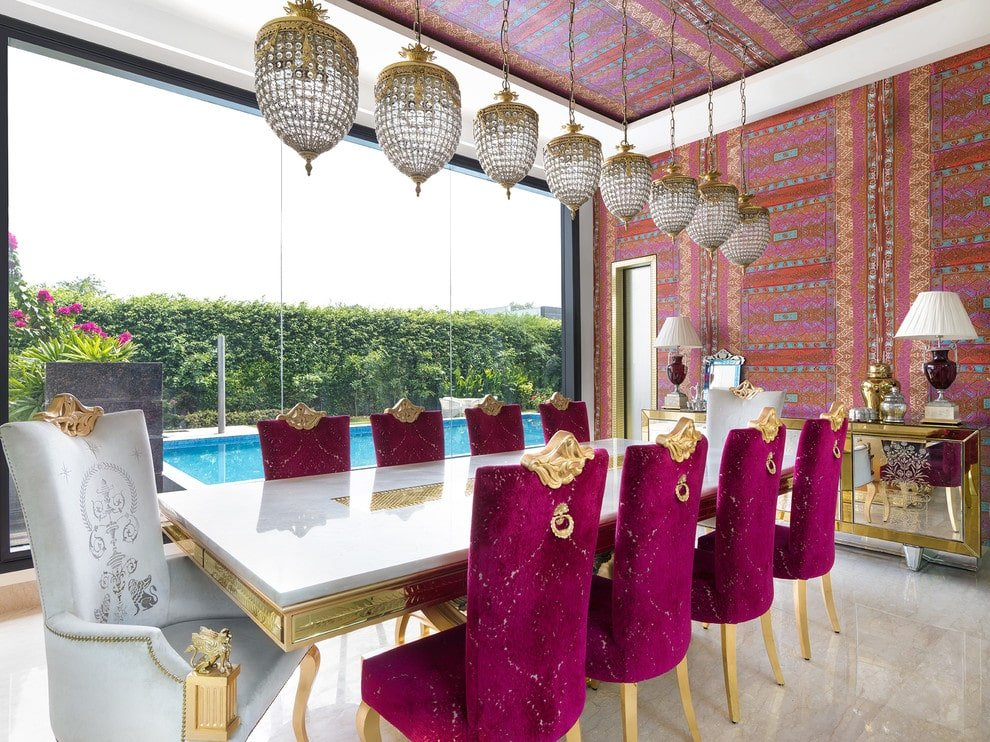 Colorful dining room with a touch of elegance from the mirrored buffet table and elegant chairs along with a white dining table that's inlaid with gold accents. It has marble flooring and a panoramic window with a view of the sparkling pool.