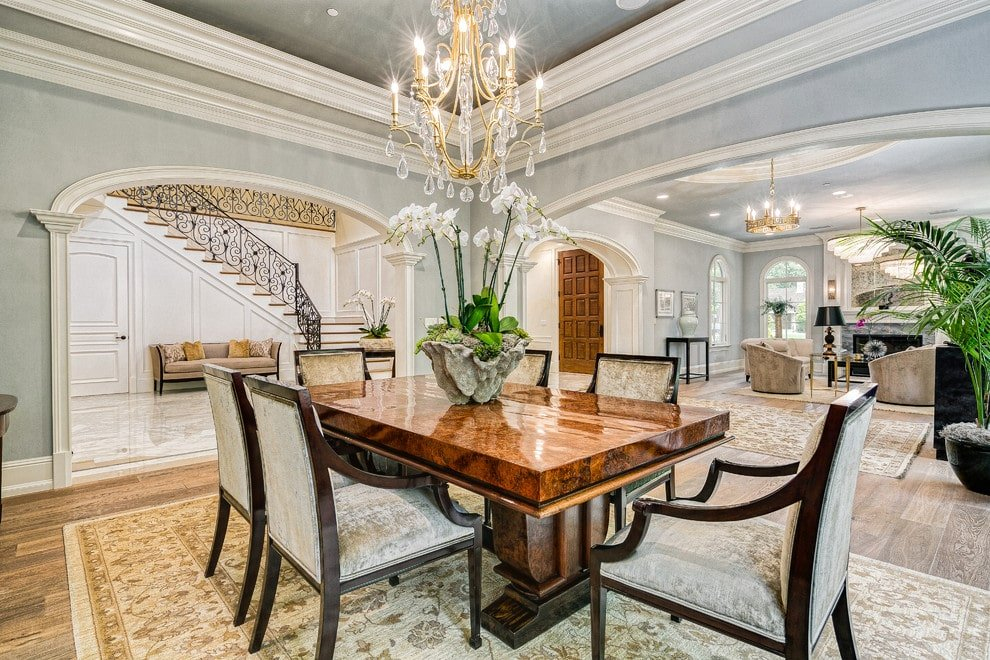 An open concept house with a luxury dining room showcasing velvet armchairs and a polished dining table on a classic rug lighted by a brass chandelier. It is surrounded by light blue walls and open archways leading to different areas of the house.