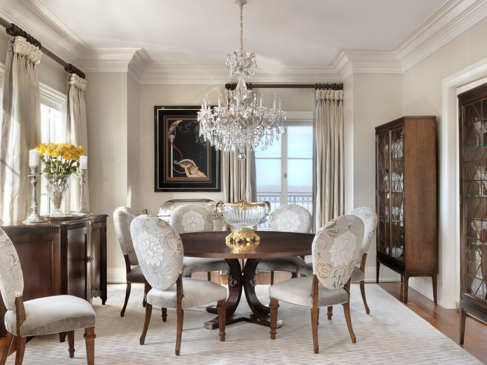 A fancy crystal chandelier is the focal point in this classy dining room with round back chairs and a wooden dining table topped with a lovely glass bowl. It is accompanied by display cabinets and a buffet table over a beige rug.