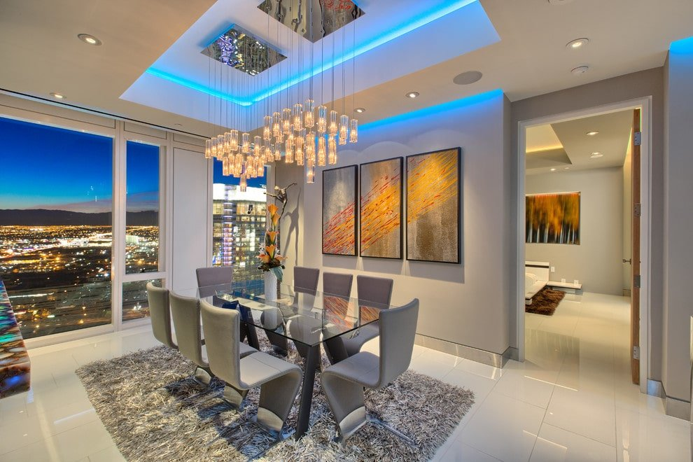 This dining room features stylish gray chairs and a glass top dining table lighted by cluster chandeliers that hung from the luminous tray ceiling. It has white tiled flooring and full height glazing overlooking the stunning city lights.