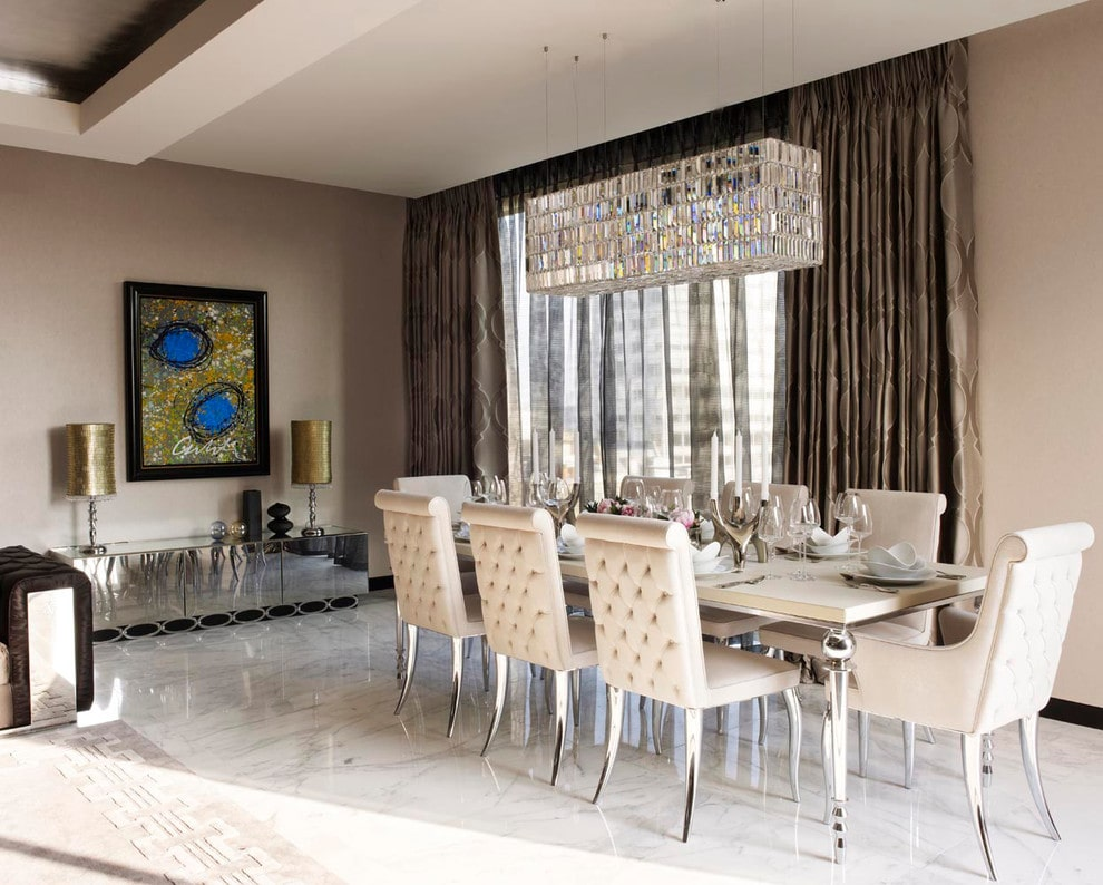 Luxury dining room styled with a sleek chandelier and an abstract painting that hung above the mirrored console table. It has a cream dining table and tufted chairs fitted with stylish chrome legs.