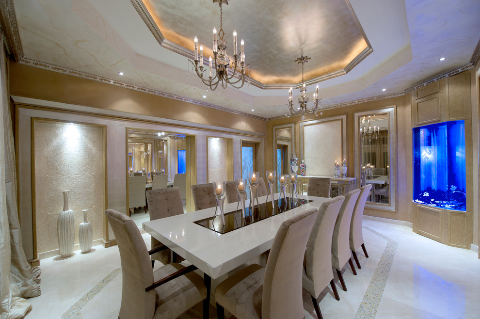 Luxury dining room designed with elegant pieces from the vases, chandeliers and stylish candle holders that sit on the white dining table. There's a fish tank on the side that stands out against the beige walls.