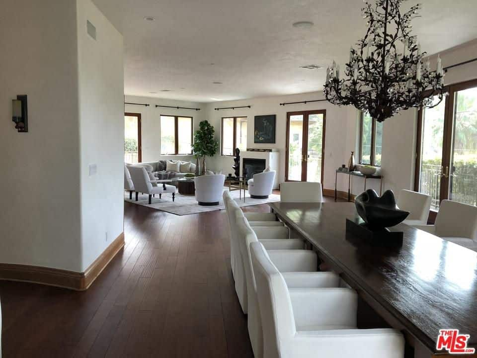 White cushioned chairs add a striking contrast to the gorgeous chandelier and dark wood dining table that blends in with the hardwood flooring. This open dining area shares the same space with the living room.