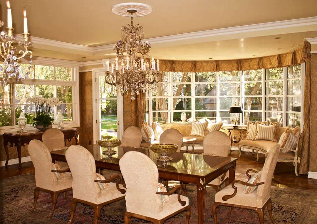 Warm dining room with a tray ceiling and white framed windows overlooking the serene yard. It offers a wooden dining set accompanied by a buffet table and curved sofas accented with striped pillows.