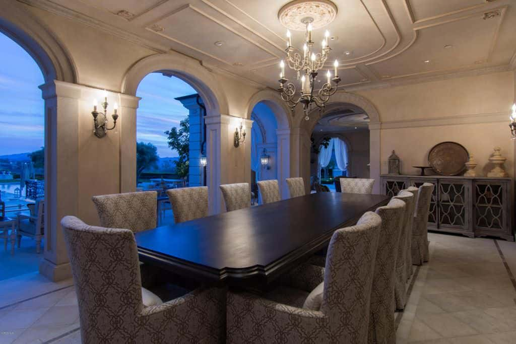 An ornate wrought iron chandelier hangs over the black dining table paired with patterned armchairs. It is surrounded by open archways and concrete walls mounted with candle sconces.