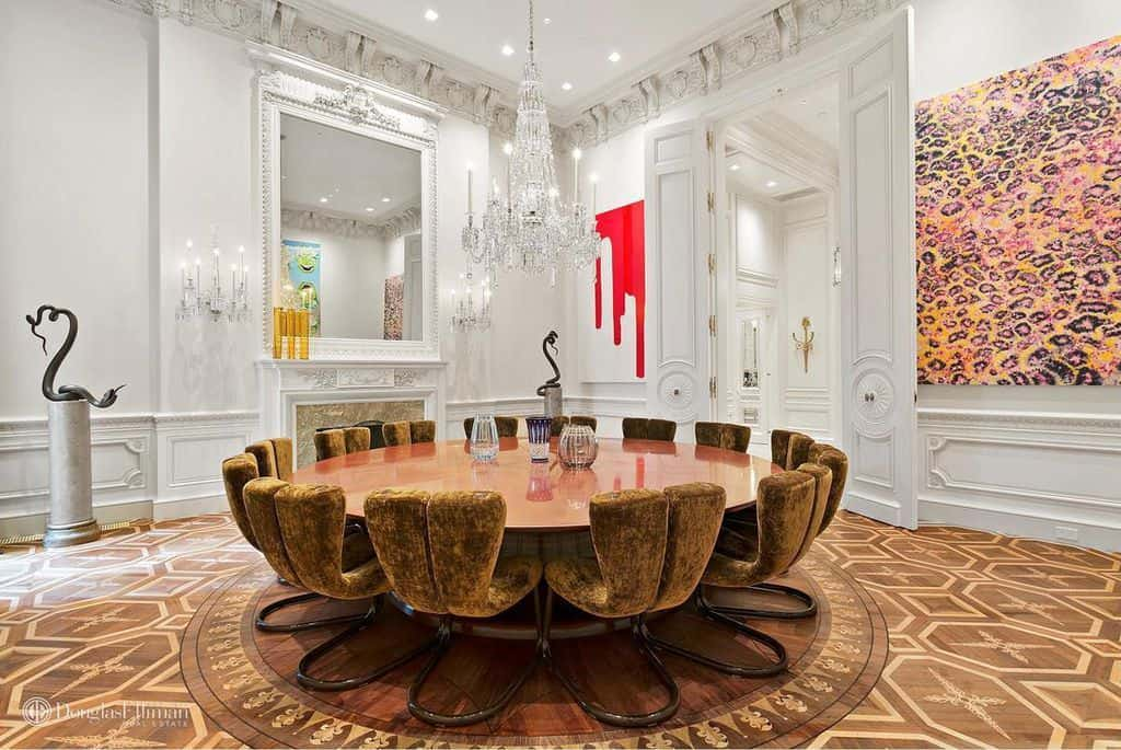 The elegant dining room boasts unique velvet chairs and a round dining table illuminated by a crystal chandelier. It is accompanied by large artworks and a fireplace under an ornate mirror.
