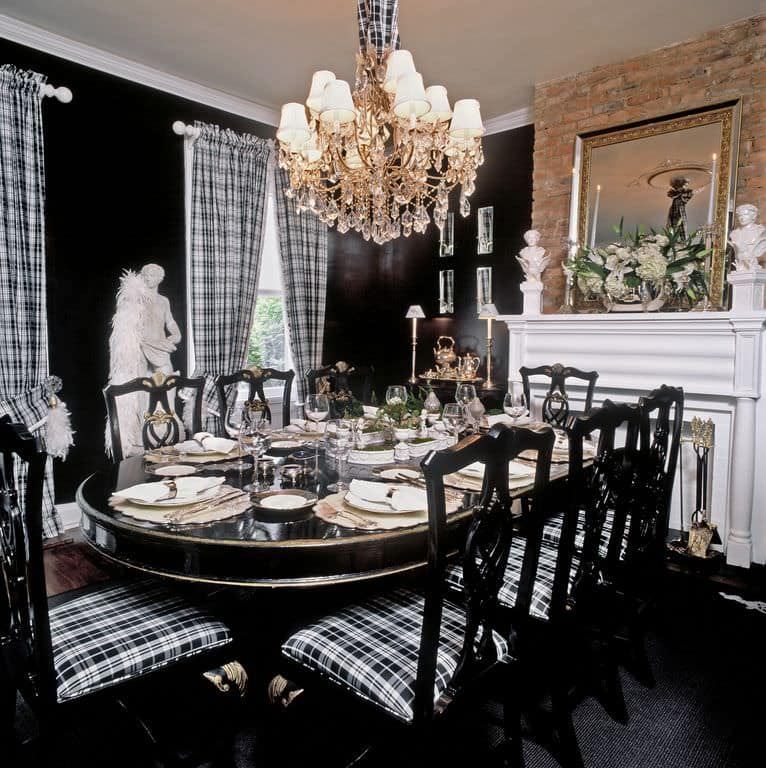 This dining room is decorated with marble sculptures and a glamorous chandelier that hung over the oval dining table surrounded by plaid cushioned chairs. It includes a framed mirror and a fireplace fixed against the brick accent wall.