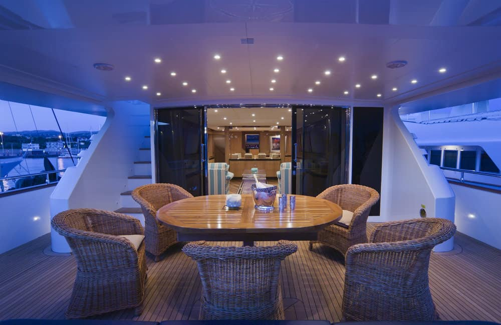Large dining table and chairs on rear lower covered deck on mega yacht.