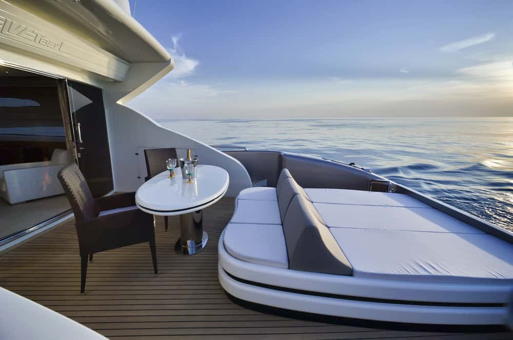 Lounge bed on rear lower deck of yacht along with small dining table and deck chairs.