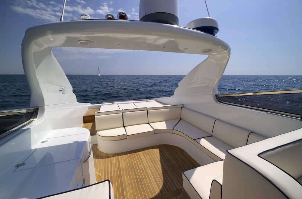 Rear deck area of open flybridge with u-shaped sectional sofa on beautiful yacht.