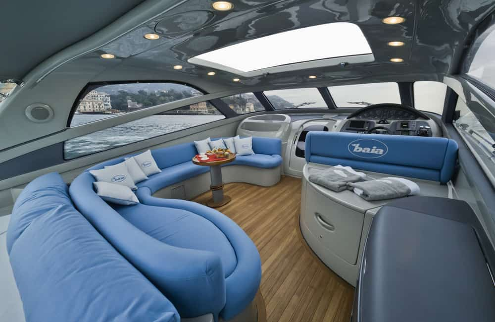 Flybridge deck on large yacht with blue curved patio sofa.