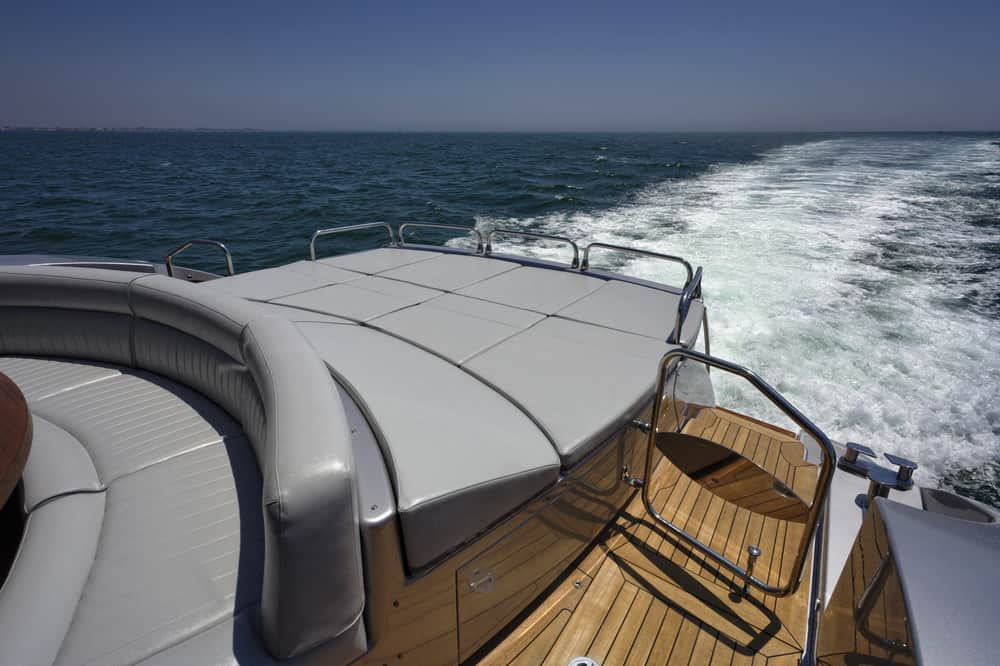 Rear deck with huge lie-down padded surfaces and built-in curved sofa seating (gray) on massive yacht motoring on the ocean.