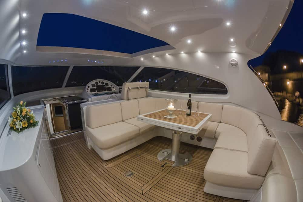 Large built-in dinette on covered flybridge of luxury yacht.