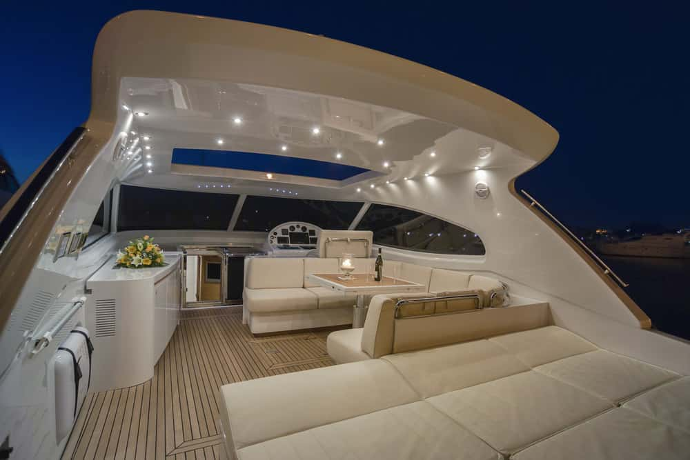 Luxury flybridge deck on yacht partially covered with loads of beautiful plush white lounge seating.