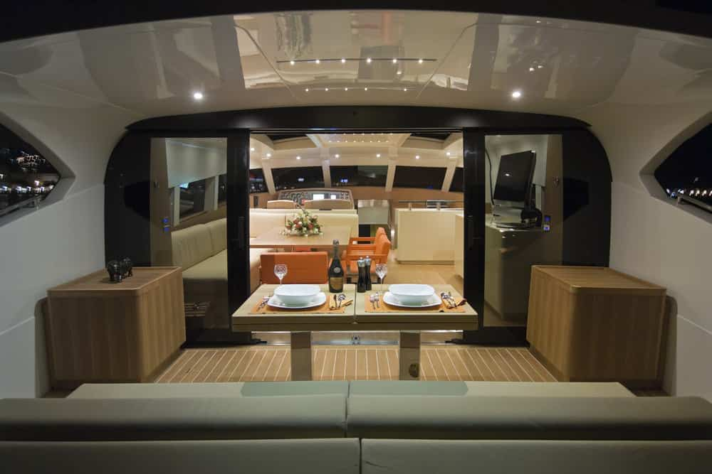 Rear lower deck with dining table and built in sofa seating. Doors enter yacht cabin.