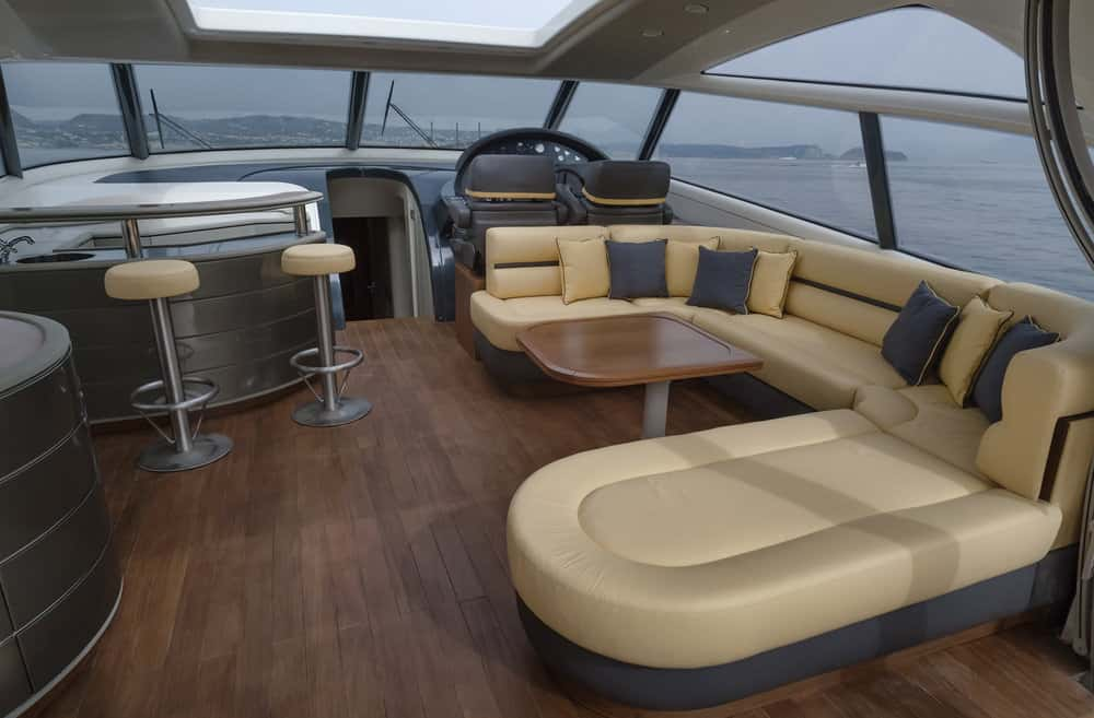Luxurious flybridge deck with beige sectional sofa and dinette. Small bar with two stools in corner next to captain's chair.