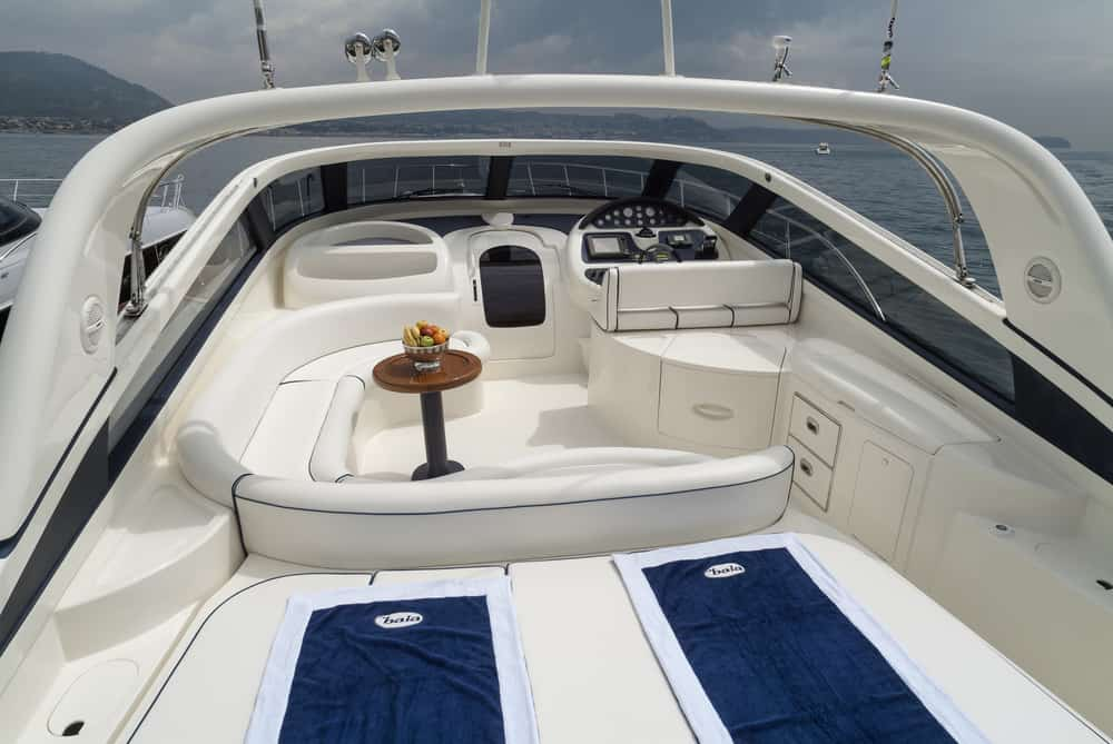 Uncovered flybridge with u-shaped white sofa and deck beds on luxury yacht.
