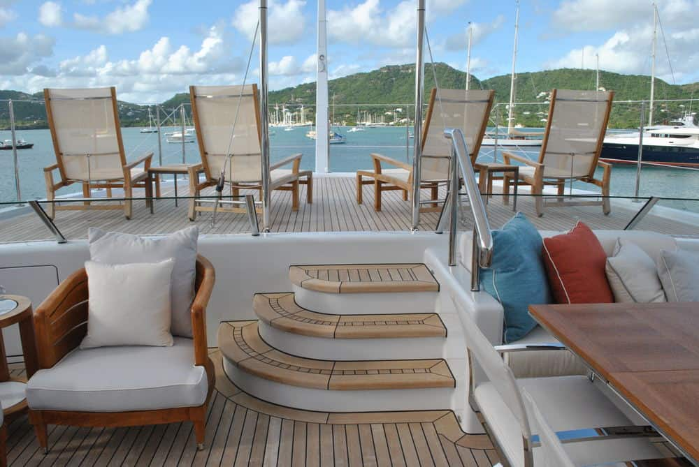 Two level rear deck on mega yacht with plenty of deck chairs overlooking harbor.