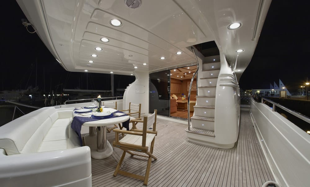 Gorgeous lower rear deck with built-in sofa seating with dinette. Stairs lead up to flybridge and door leads into cabin.