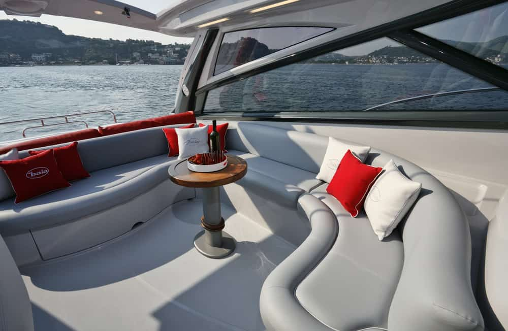 Curved gray bult-in patio sofa on flybridge of motor yacht.