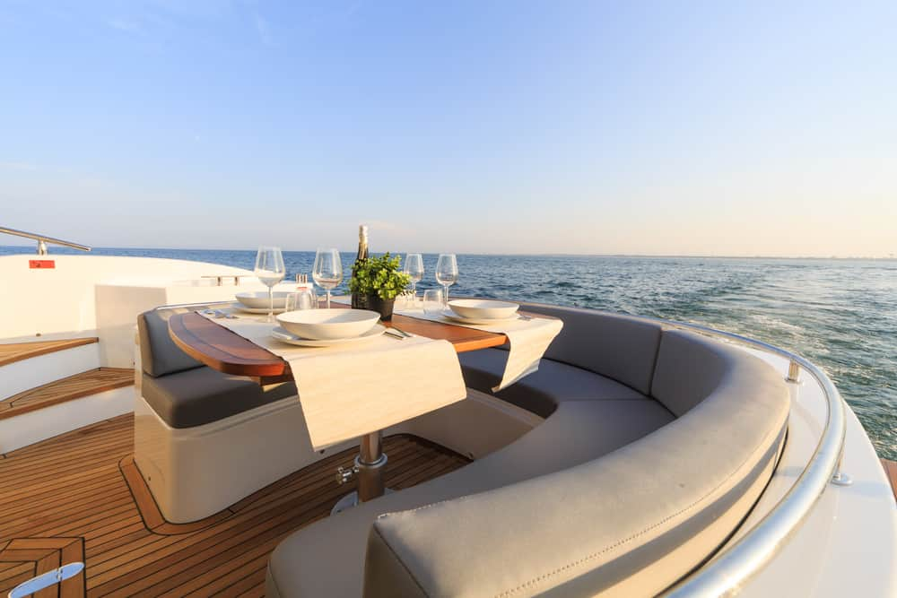 Stylish curved bench seating on rear deck of yacht with table set for breakfast.