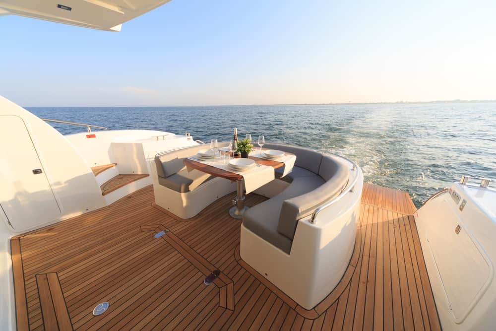 Stern deck built-in curved dinette seating and table on gorgeous yacht.