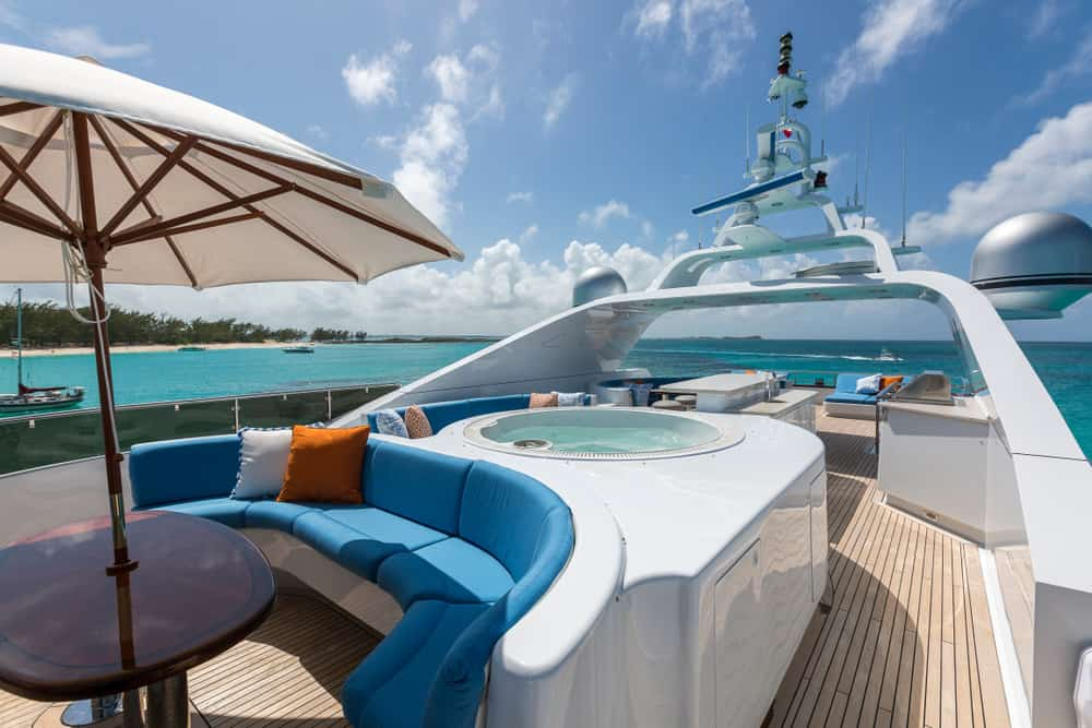 Flybridge deck with built-in curved blue sofa and jacuzzi.