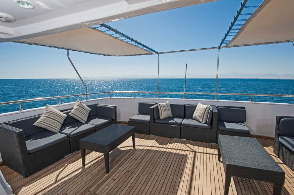 Large wooden rear stern deck on mega yacht with black sofas. Partially covered.